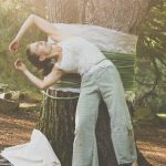 woman dances in front of tree